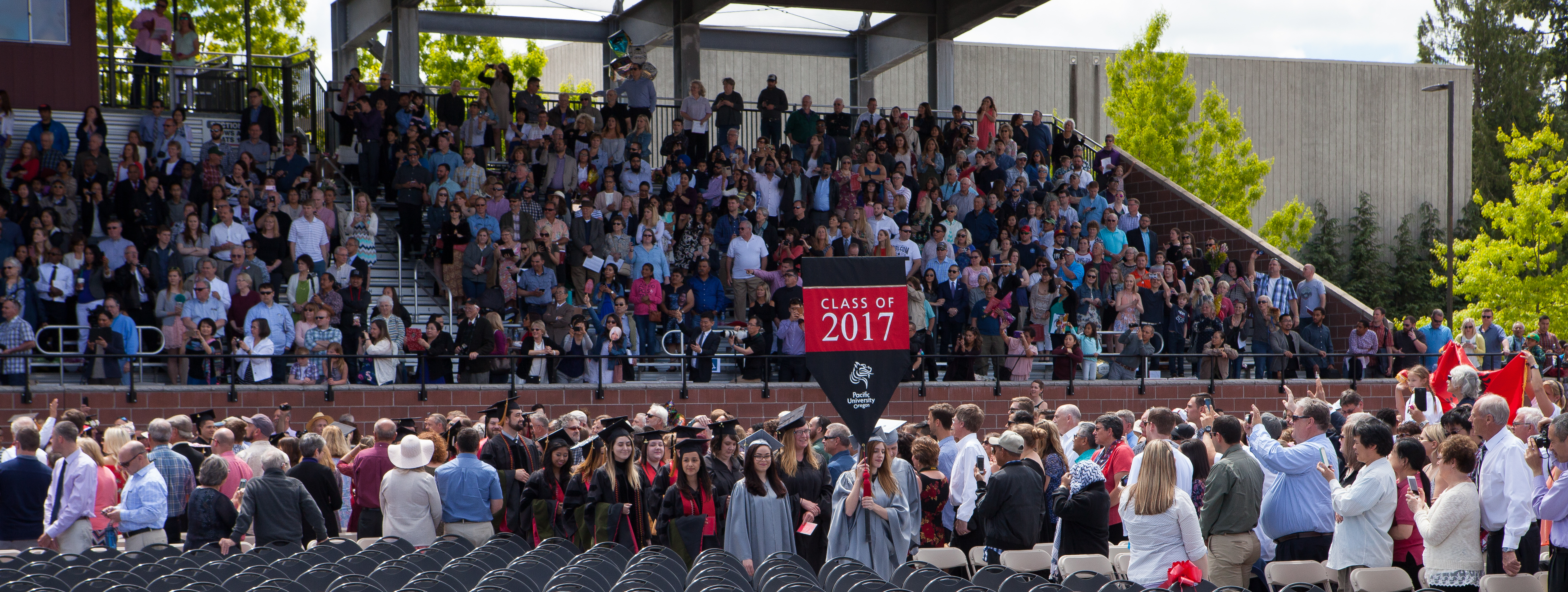 Visitors in bleacher seating watching mencement processional