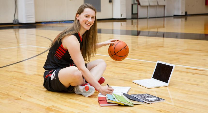 Charli Elliott dribbles a basketball amid books and a computer on the court
