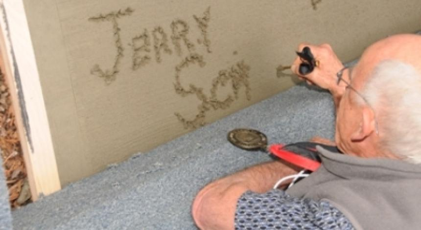 An alumnus carves his name in wet cemet