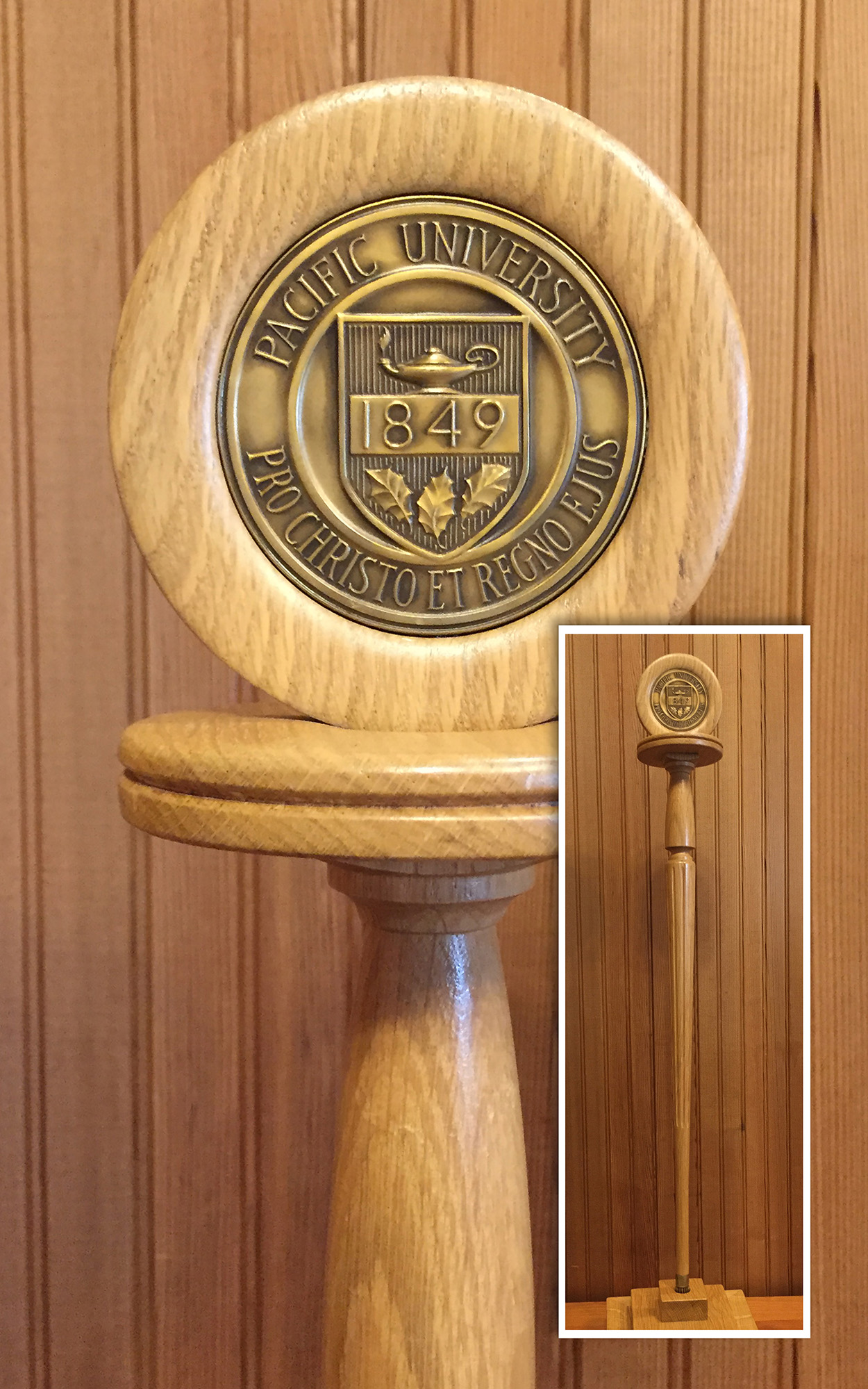 Wooden staff with a brass university seal topper