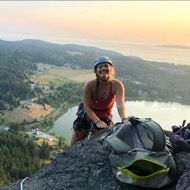 Bella Jackson, Outdoor Pursuits Instructor, posing at the top of a climb