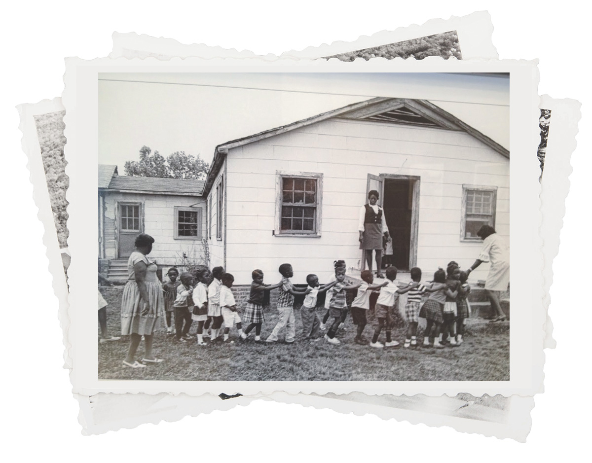 Young children seated outside schoolhouse
