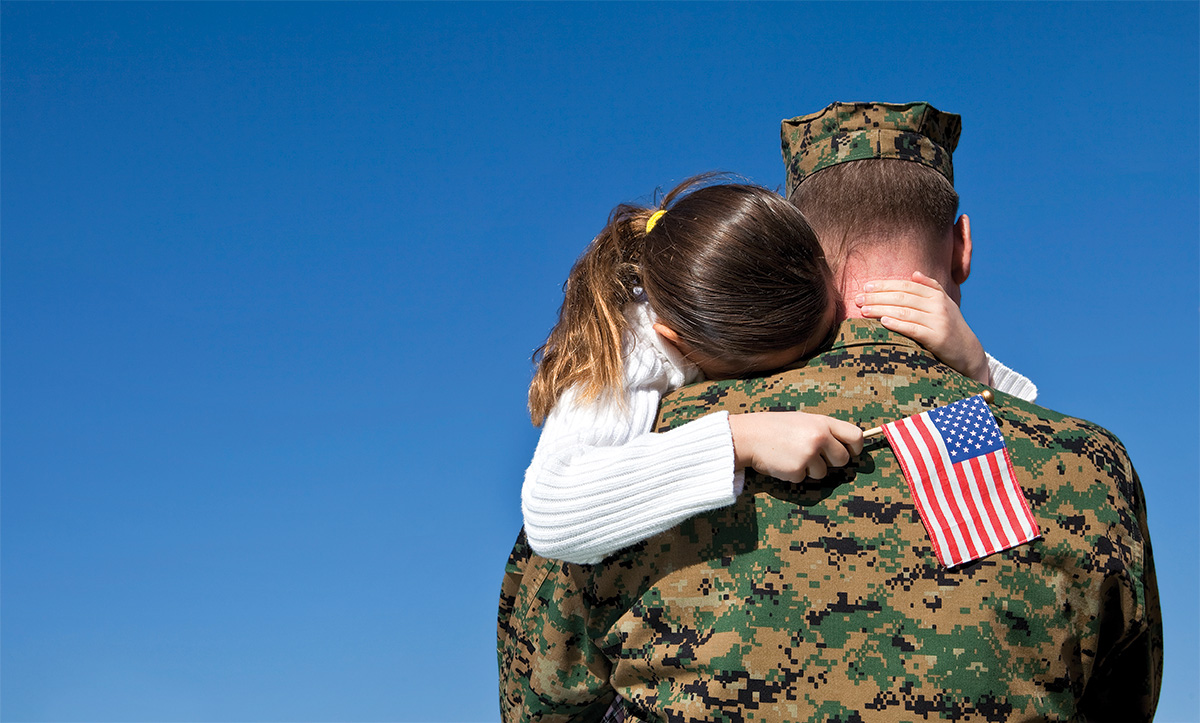 Soldier hugging young girl