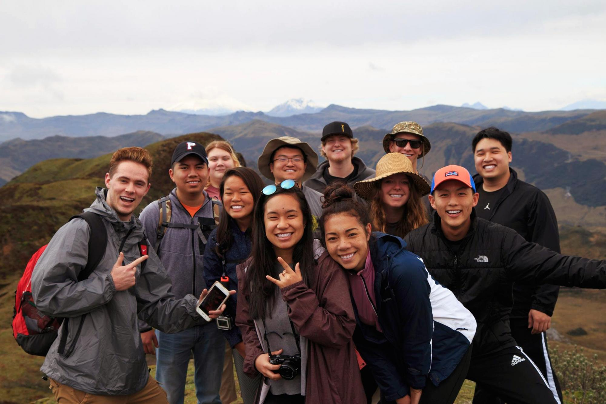 Students abroad smile at the camera with mountains and clouds in the background.