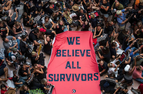 "People holding a banner reading ""We believe all survivors"""