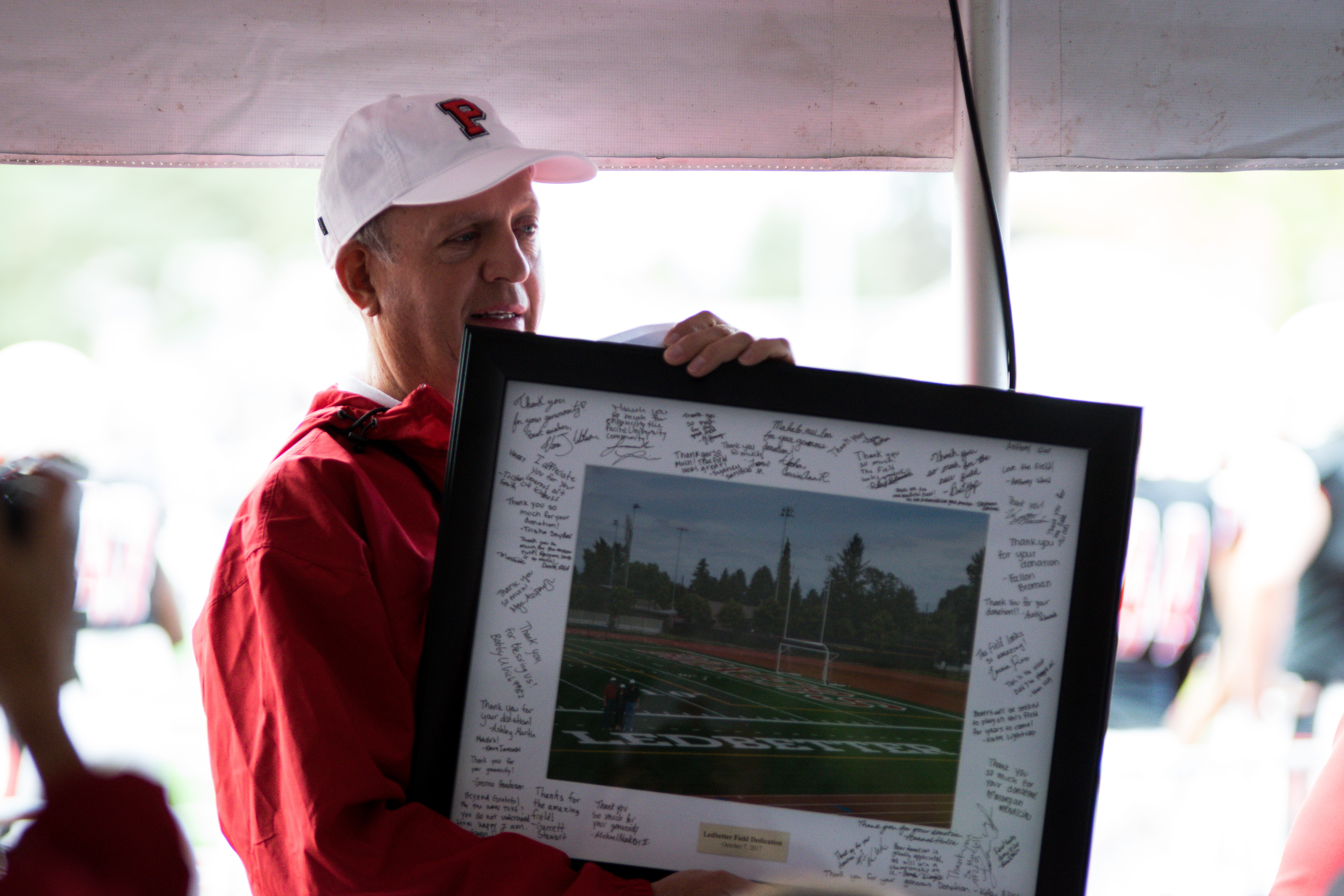 Kim Ledbetter holds a signed photo of Ledbetter Field