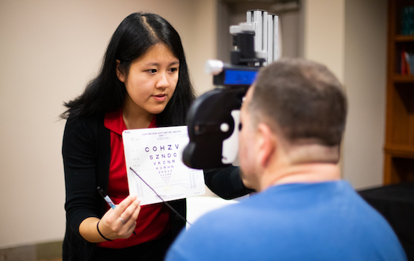 Optometry student holds up exam sheet for patient