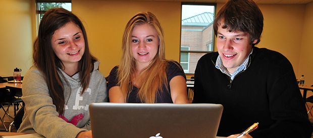 Three students share a computer