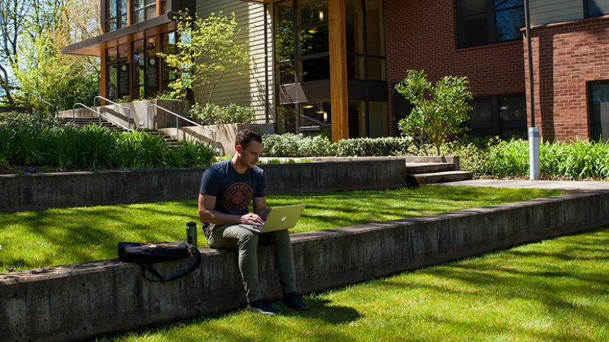 Student with laptop in lawn