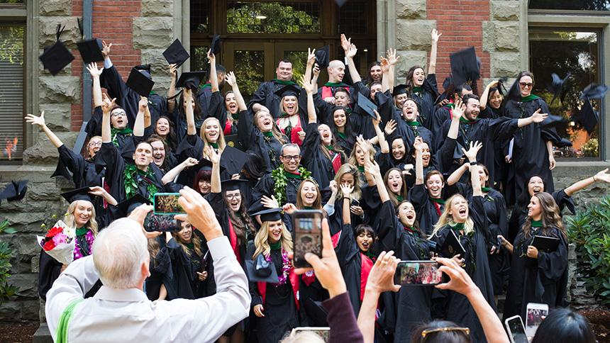 A group of August 2019 Pacific University graduates tossing caps on Marsh Hall steps while families take photos