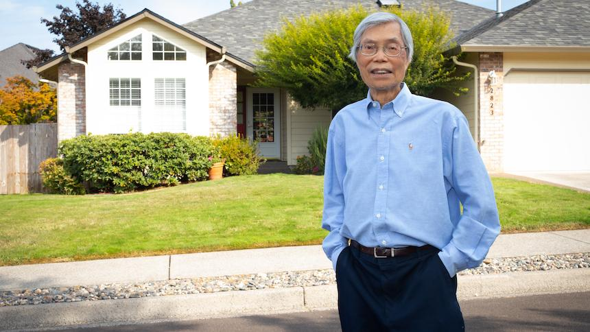 Tim Tran in front of a house