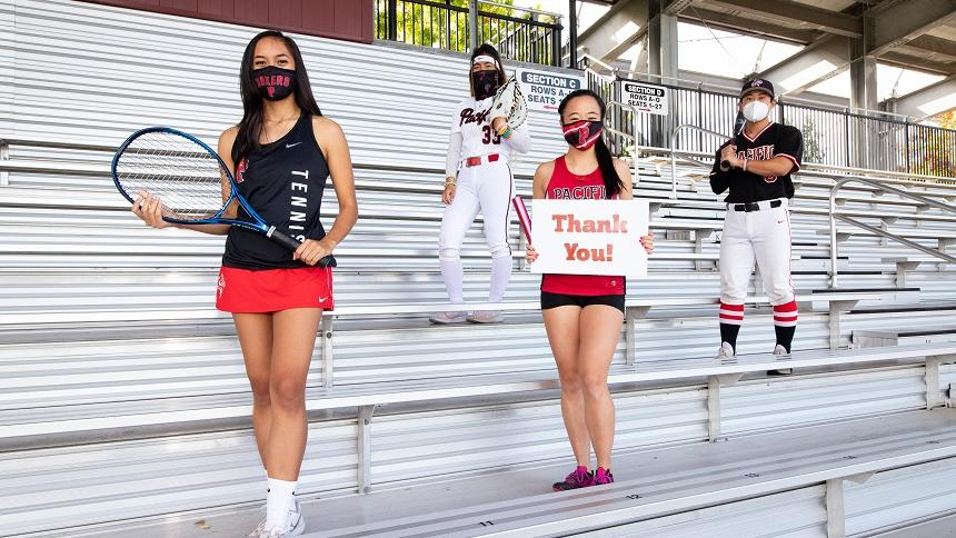 """SAAC executive board members in the stands holding a """"thank you"""" sign"""