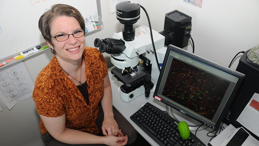 Amber Buhler with microscope and computer, from a Pacific file photo