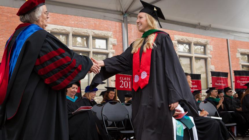 graduating student shaking hands with President Hallick at August Commencement