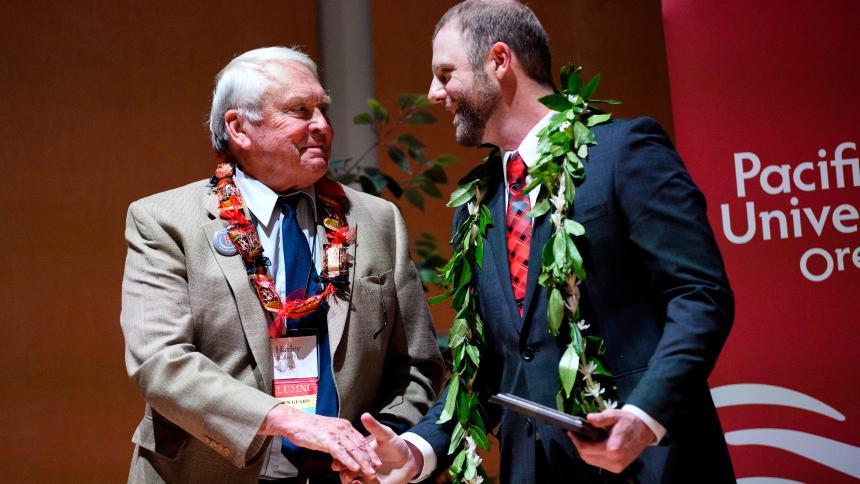 Alumni and student shake hands