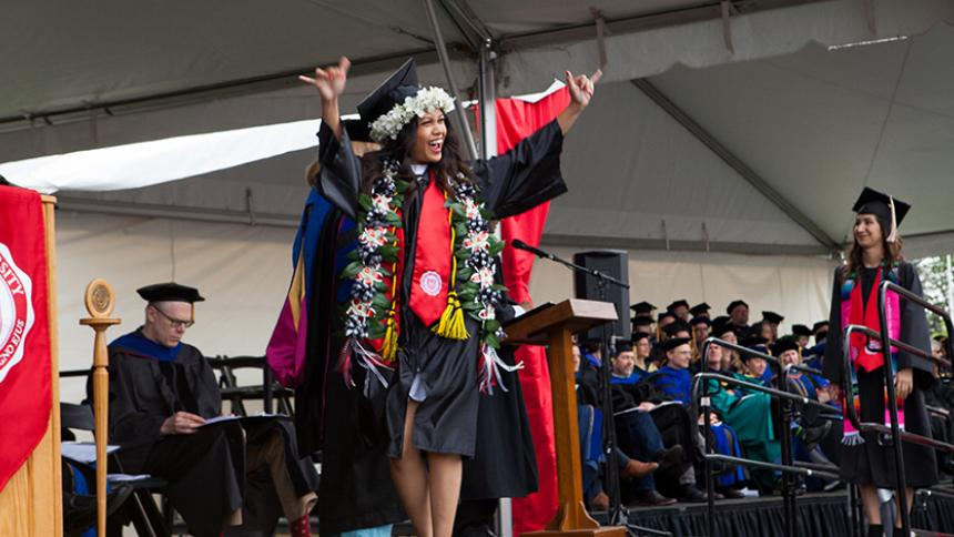 Student wearing leis celebrates commencement