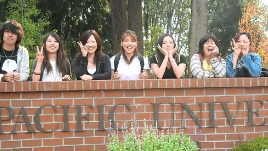 International Students pose in front of Pacific University sign