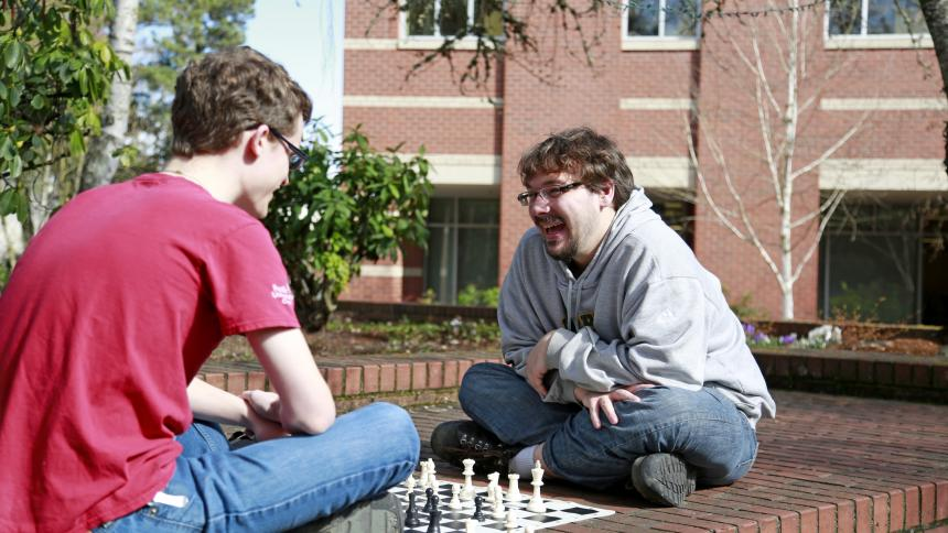 Two male students playing chess on a brick ledge