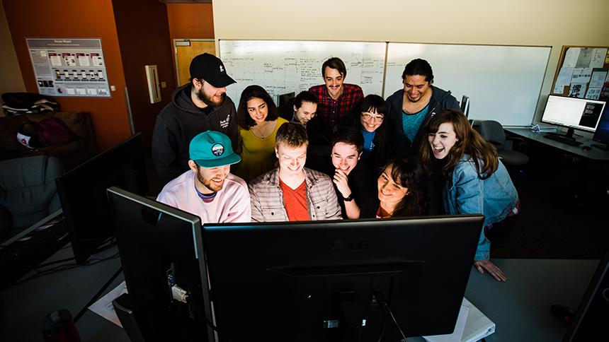 Students and professor huddled around computer screen in computer science class