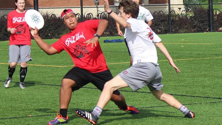 Two male students playing Ultimate Frisbee