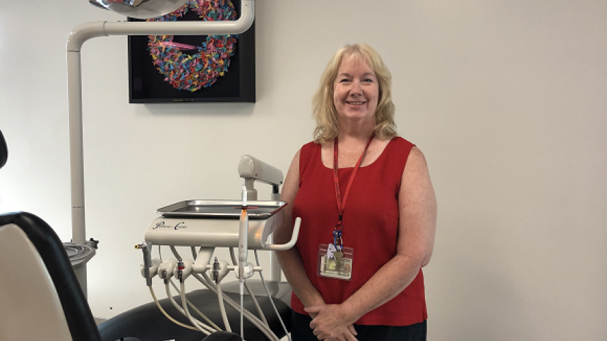 Dental Hygiene Studies founding director Lisa Rowley stands in program's clinic next to a dental chair