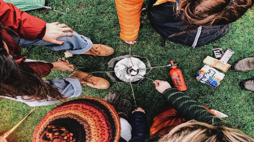 A group of students gather around a campfire for s'mores.