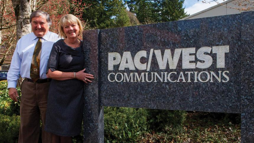 Paul and Nancy Phillips posing in front of PacWest Communications.