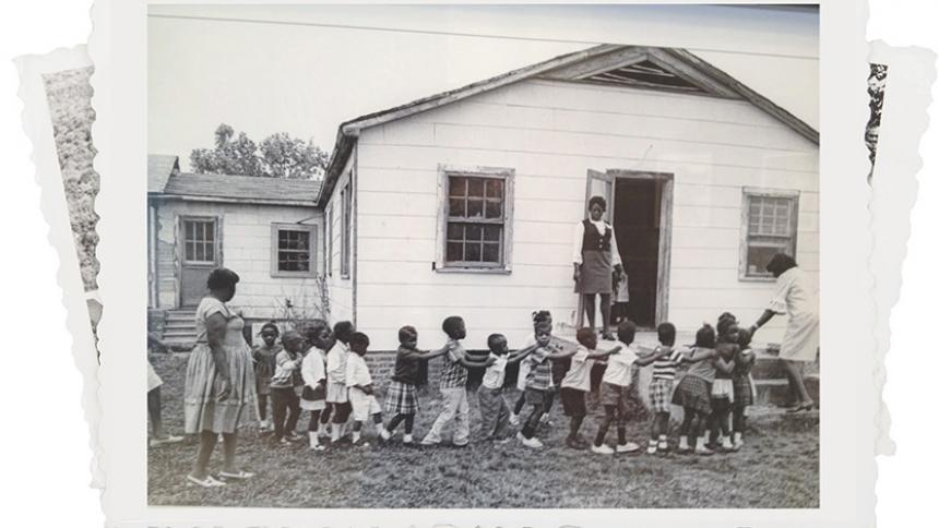 Young children walking out front of the school house.