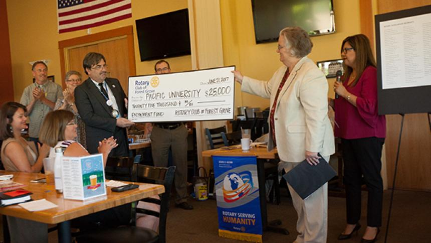 President Hallick receives a commemorative check from the Rotary Club of Forest Grove.