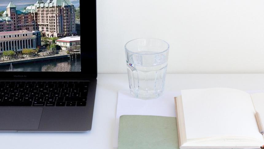 White desk with a computer, notebook, and glass of water on it.